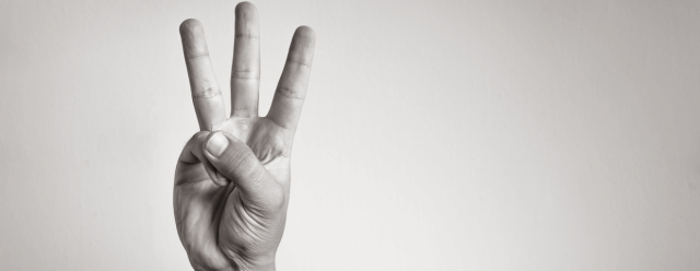 Black and white photo of a hand gesturing number 3 on blank background