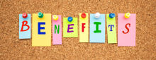 Colorful sticky notes on cork board that spell out the word benefits