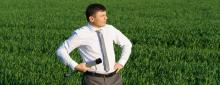 Business man in the middle of a field holding a spyglass with his hands on his hips and a quizzical look on his face