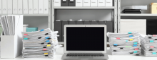 Laptop on desk full of documents with files on shelves in background